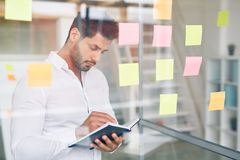 Workflow. Serious employee standing by note board and rewriting organization moments into his notebook Royalty Free Stock Photos