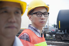 Serious engineer in protective workwear looking at camera outside in front of railroad tracks Royalty Free Stock Photos
