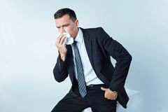Serious entrepreneur in suit sneezing hard over background. Caught an illness. Chopped shot of a bit confused man sitting on a studio cube and using a paper Royalty Free Stock Image