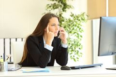 Serious executive calling on phone checking computer stock image