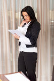 Serious executive woman reading in office Royalty Free Stock Photos