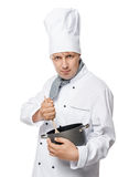 Serious experienced cook mixing with a wooden spoon food. In a pot on a white background stock photo