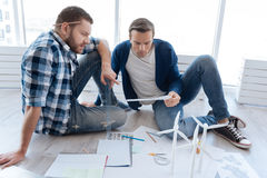 Serious experienced engineers focusing on their work. Environmental project. Serious experienced male engineers looking at the draft and discussing it while royalty free stock images
