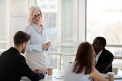Serious experienced team leader discussing with colleagues at meeting. Diverse workers sitting at desk listen experienced coach company owner female boss royalty free stock photo