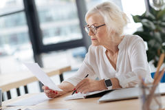 Serious experienced woman doing her job. Corporate manager. Serious smart experienced woman reading the document and taking noted while doing her job royalty free stock photography