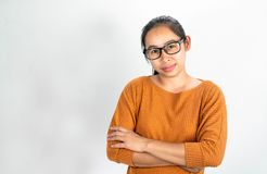 Serious face Asian woman waring orange shirt and eyeglasses; Standing and crossing one`s arm  on a white background. Serious face Asian woman waring orange shirt royalty free stock images