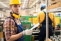Serious factory employee responsible for quality control. Serious confident handsome factory worker in hardhat and soundproof headphones holding clipboard with royalty free stock photos