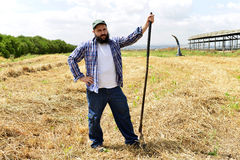 Serious farmer leaning on his fork after hard work day. The farmer just finished working his field. Pleased with his work he can now take a break royalty free stock photo