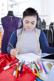 Serious fashion designer draws sketch Royalty Free Stock Photos