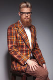 Serious fashion man with long beard sitting. Serious fashion man with long beard and great hairstyle sitting on a chair and looks at the camera stock photo