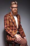 Serious fashion man with long beard sitting stock photo