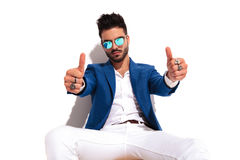 Serious fashion man sitting and makes the ok sign. Serious fashion man sitting and makes the ok thumbs up hand sign on white background Royalty Free Stock Photos