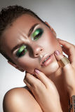 Serious fashion model with beautiful green makeup looking down Stock Photos