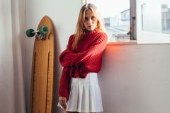 Blonde model in cute outfit with longboard Royalty Free Stock Image