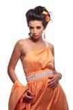 Serious fashion woman in a corai dress Stock Photos