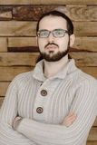 Serious fashion young man in eyeglasses with beard on wood background Royalty Free Stock Photography
