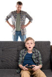 Serious father with hands on waist looking at son sitting on sofa with joystick. Family problems concept stock image