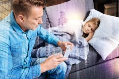 Serious father holding a pillbox while his ill child sleeping. Necessary pills. Attentive caring father sitting on the sofa with a pillbox in his hand and Stock Photo