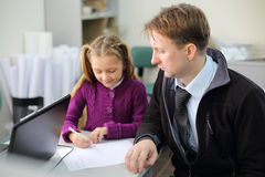 Serious father looks at his little daughter drawing picture Royalty Free Stock Photo