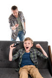 Serious father pointing with finger and excited son sitting on sofa with joystick. Family problems concept Royalty Free Stock Photography