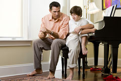Serious father talking to teenage son at home stock image