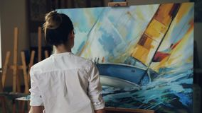 Serious female artist is working at picture using oil paints and palette-knife creating beautiful marine landscape on stock video footage