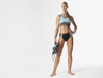 Serious Female Athlete Holding Shoes Stock Image