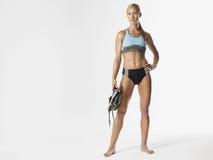 Serious Female Athlete Holding Shoes Stock Image