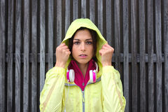 Serious female athlete wearing sport raincoat with hood Stock Photography
