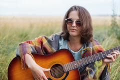 Serious female with attractive appearance wearing sunglasses sitting at meadow with acoustic guitar trying to play song. Young fem Stock Photos