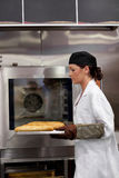 Serious female baker with baguettes Royalty Free Stock Photo