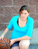 Serious female basketball player. Serious female basketball player with an attitude posing with ball outside stock photography