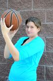 Serious female basketball player. Serious female basketball player with an attitude posing with ball outside stock photos