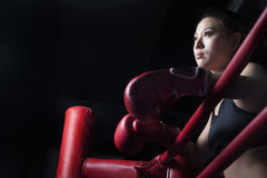 Serious female boxer resting her elbows on the ring side, looking away, low angle view Stock Photography