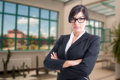 Serious female broker standing with folded arms Stock Photo
