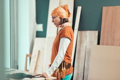Serious female carpenter thinking about project stock images