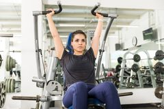 Serious Female Client Doing Shoulder Press In Health Club. Serious female client looking away while doing shoulder press in health club royalty free stock photos