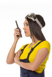 Serious female construction worker talking with a walkie talkie Royalty Free Stock Images