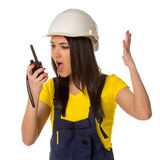 Serious female construction worker talking with a walkie talkie Stock Photo