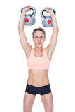 Serious female crossfitter lifting kettlebells above head Royalty Free Stock Photo