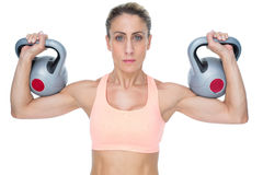 Serious female crossfitter lifting kettlebells looking at camera Stock Images