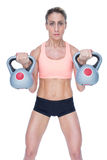 Serious female crossfitter lifting kettlebells Royalty Free Stock Photos