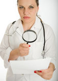 Serious female doctor analyzing document Stock Images
