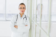 Serious female doctor with arms crossed in hospital Stock Photo