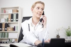 Serious Female Doctor Calling Through Telephone Stock Photo