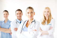 Serious female doctor in front of medical group royalty free stock photography