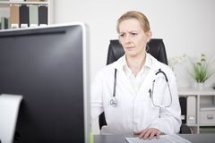 Serious Female Doctor Looking at Computer Monitor Royalty Free Stock Image