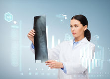 Serious female doctor looking at x-ray. Healthcare, medicine and radiology concept - serious female doctor looking at x-ray royalty free stock images