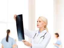 Serious female doctor looking at x-ray Stock Image