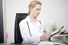 Serious Female Doctor Making Medical Findings Royalty Free Stock Photo